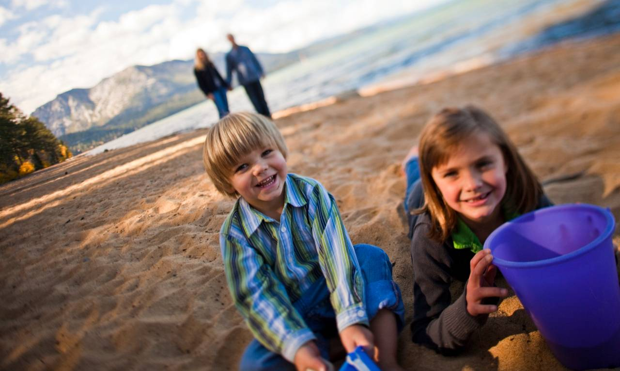 boy and girl playing in the sand in fall