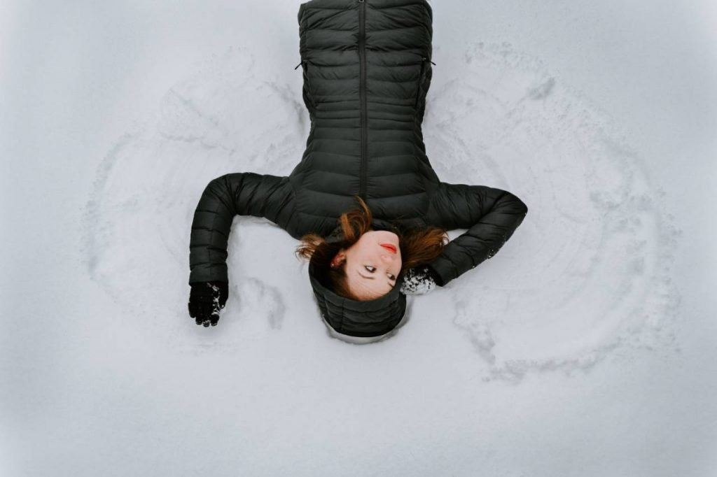 woman in black making snow angels