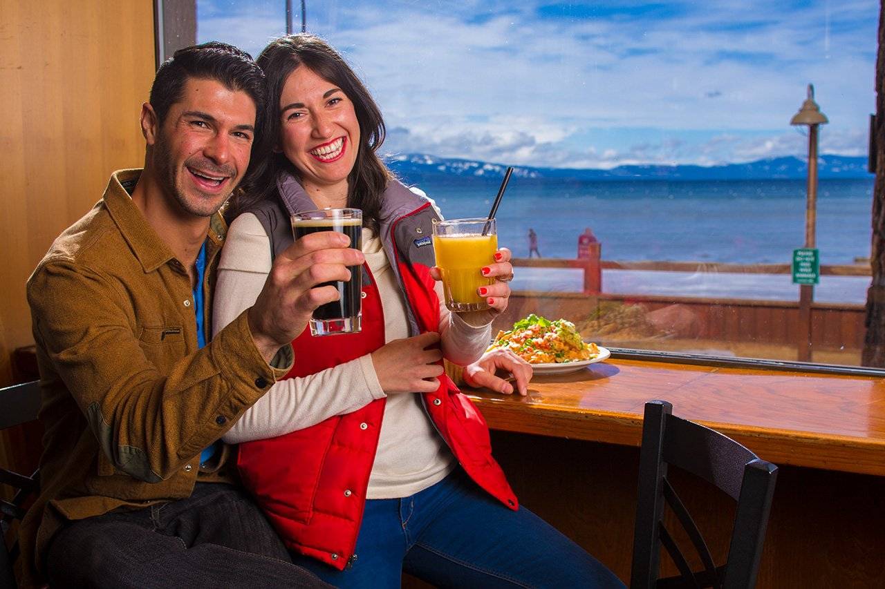 A couple enjoying a romantic Tahoe lakeside dinner at The Beacon Bar & Grill.
